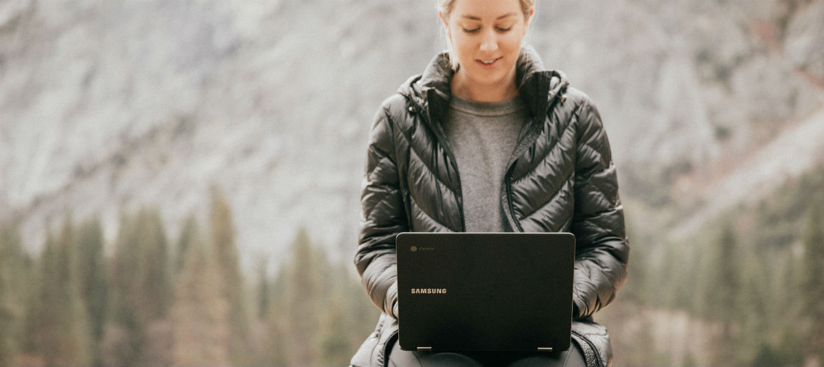 woman sitting outside in the forest working on an open laptop
