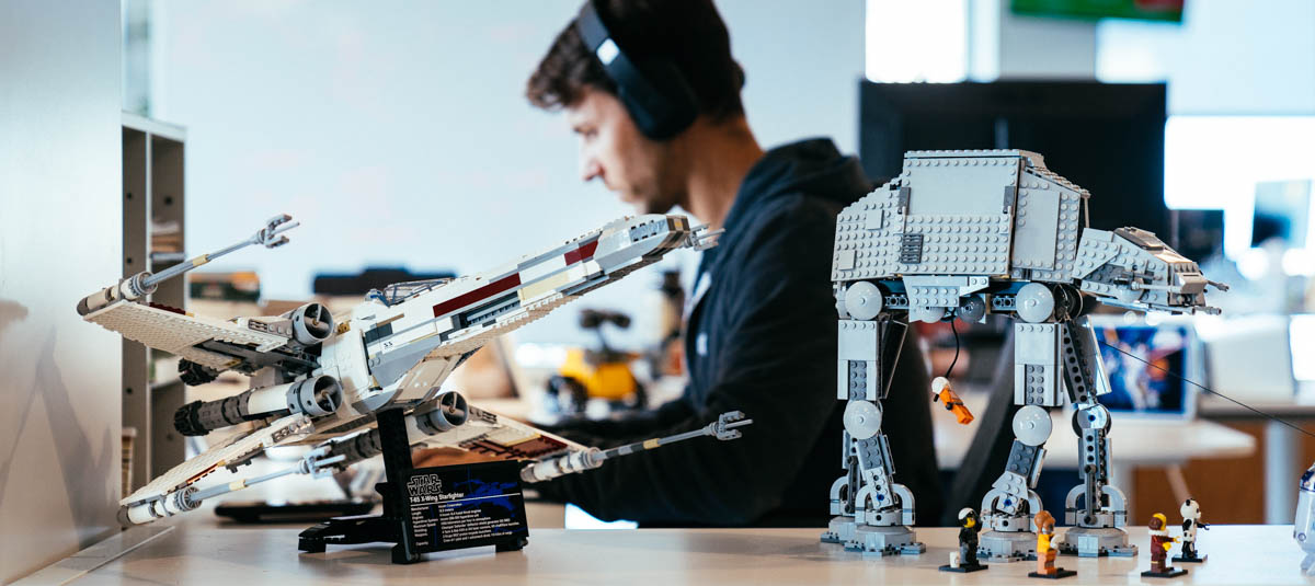 man working with headphones on and lego star wars characters