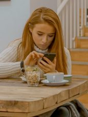 redhead woman sitting at a table with coffee and a stack of books looking at her phone