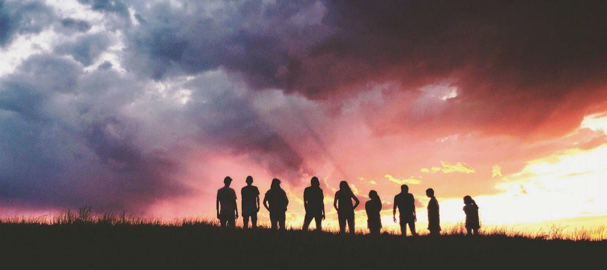 silhouette of a group of people in front of a sunset
