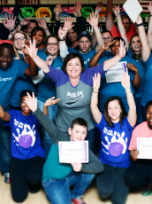 volunteers at the big brothers big sisters of america raising their hands and posing for a photo