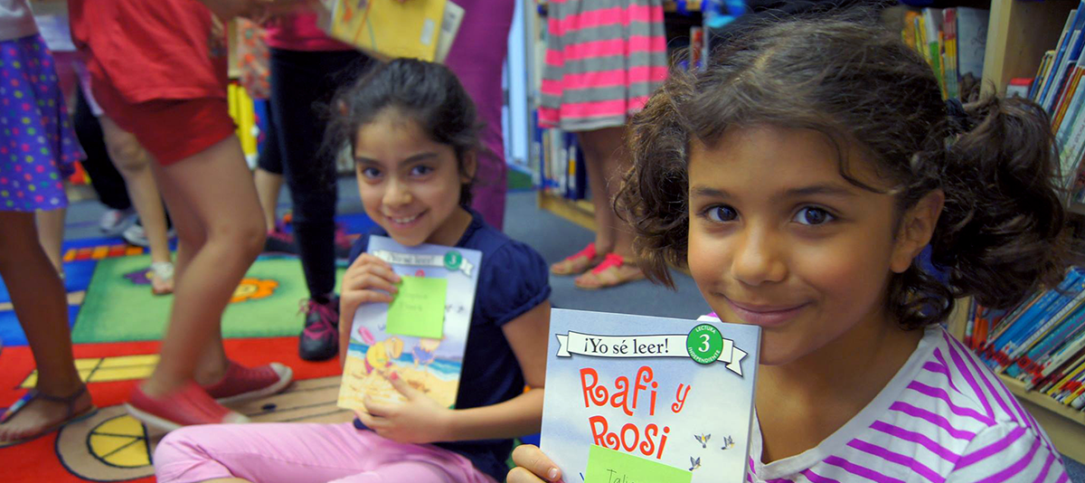 two young girls holding books and smiling