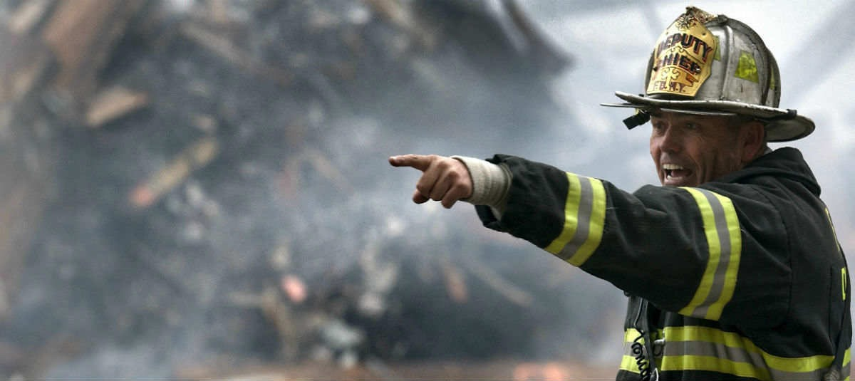 a fireman pointing at something in a fire