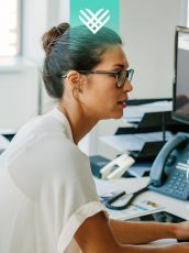 women in a white shirt with glasses working on a computer