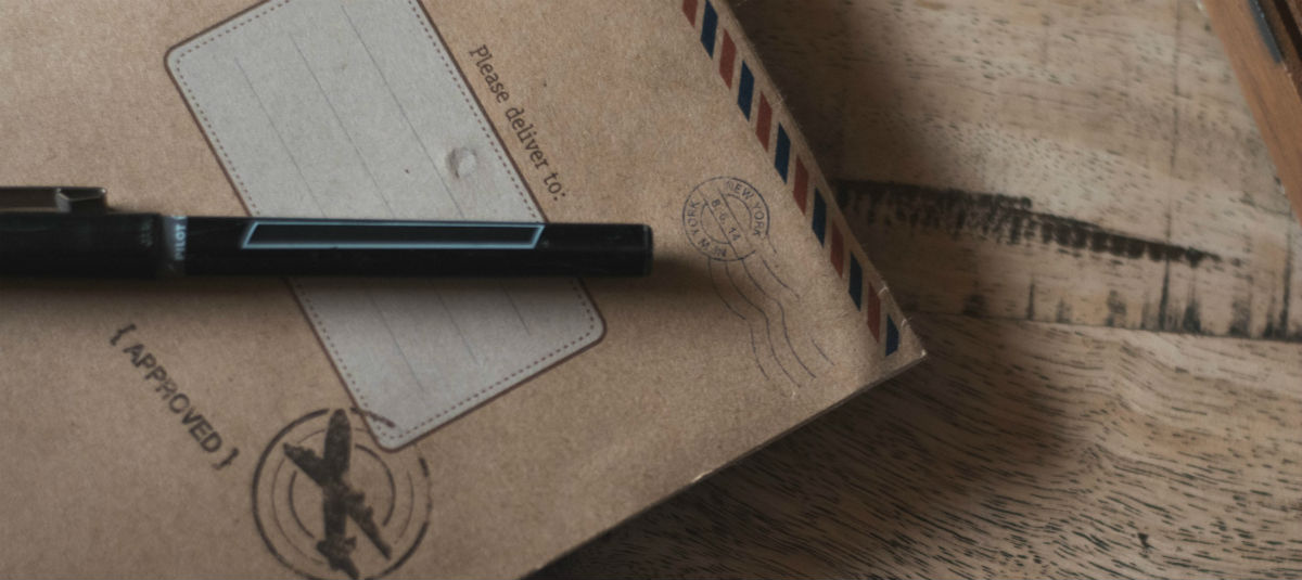 a close up of an old postcard with a pen