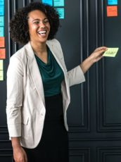 woman in a white jacket putting up post its on a board while collaborating with coworkers