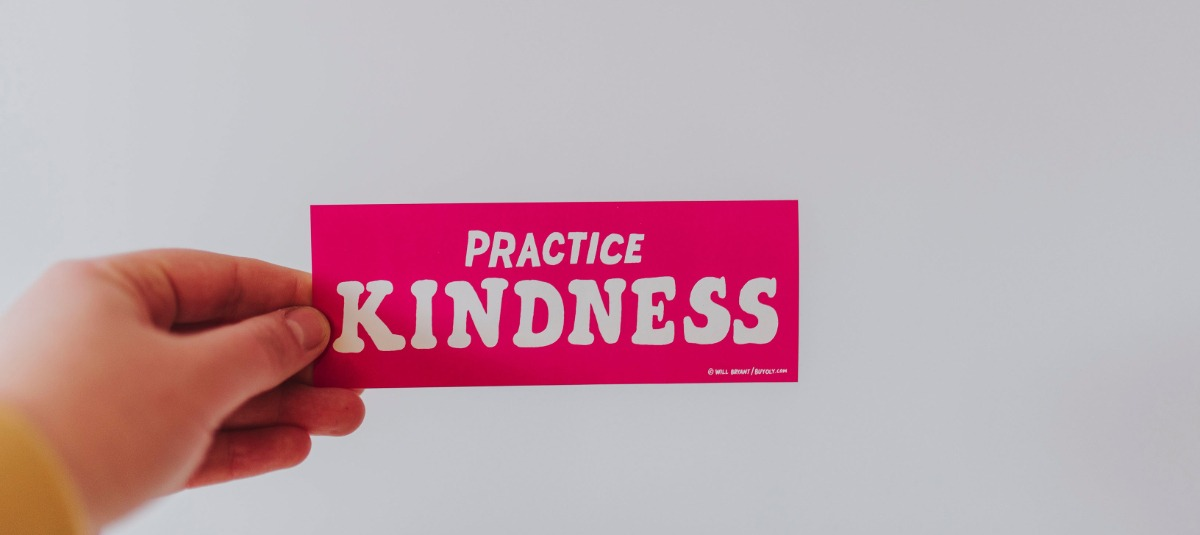 hand holding a sticker that says practice kindness