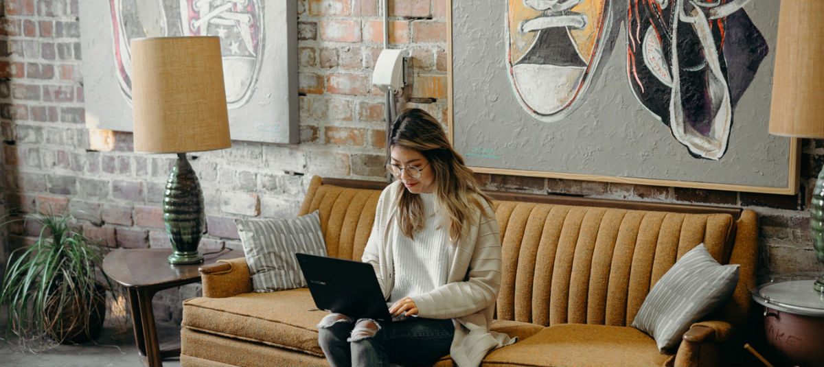 women sitting on orange couch working on an open laptop