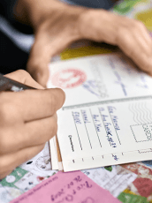 Unify offline and online fundraising tips blog header, showing a person filling out a postcard.