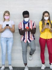 young people with masks looking at phones