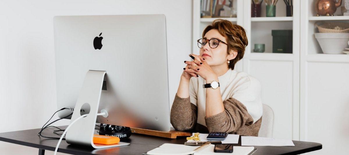 woman at computer with hands clasped
