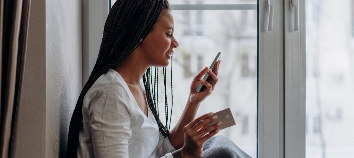 woman making recurring gift with credit card on mobile phone