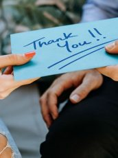 hands exchanging a thank you card