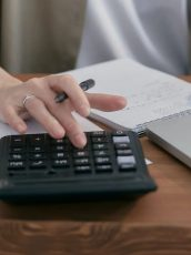 woman typing on a calculator