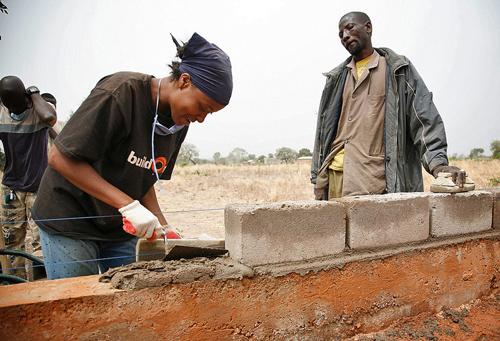 Woman lays bricks